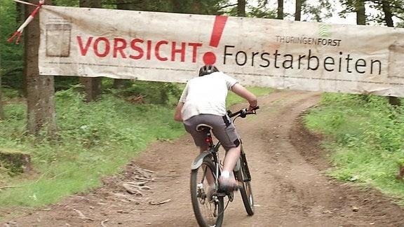 """Ein Fahrradfahrer fährt auf einem Waldweg auf ein Banner zu auf dem """"Vorsicht Forstarbeiten"""" steht."""