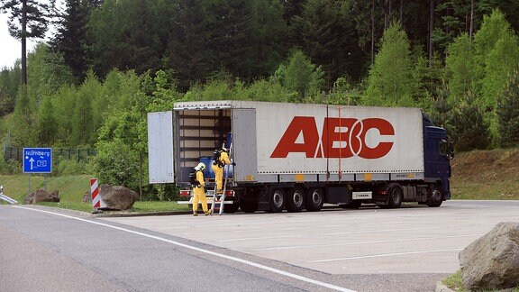 Zwei Feuerwehrleute in gelben Schutzanzügen steigen über eine Leiter in den hinten geöffneten Anhänger eines Sattelzugs auf einem Parkplatz an der Autobahn A73