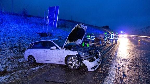 Ein weißes Auto liegt zerstört im Graben neben der Autobahn