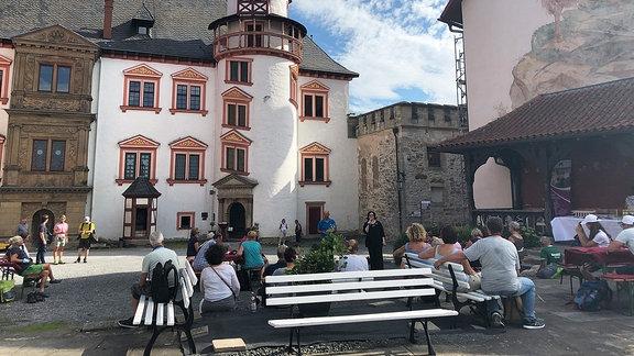 In einem Burghof sitzen Menschen auf Bänken.