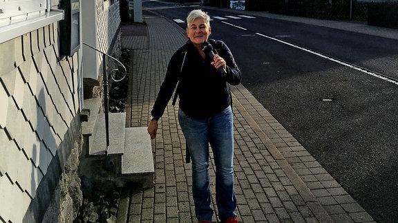 Eine Frau mit Mikrofon in der Hand steht vor einem Café