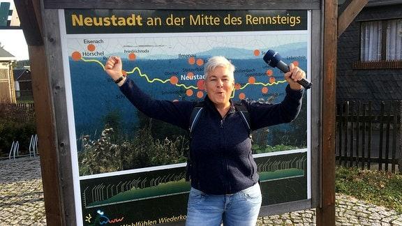 Eine Frau mit Mirkofon in der Hand reißt vor einem Schild die Arme hoch