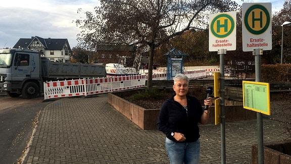 eine Frau steht vor einer Ersatzhaltestelle für Busse