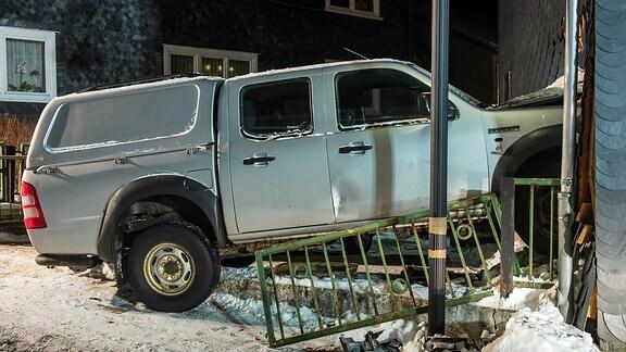 Auto steckt mit Motorhaube in Haus