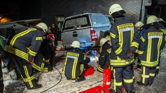 Feuerwehrleute bergen Auto aus Hauswand