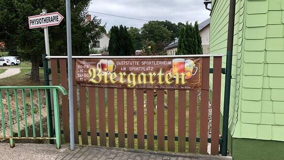 Ein Banner an einem Zaun weißt auf einen Biergarten hin.