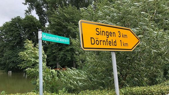 Ein Straßenschild weißt nach Singen und Dörnfeld, ein anderes, kleineres zur Museumsbrauerei.