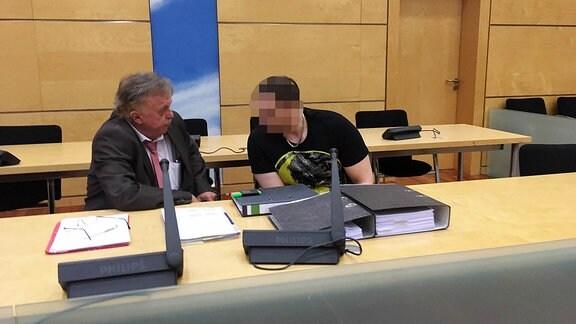 Ein Mann beugt sich im Gerichtssaal zu seinem Anwalt.