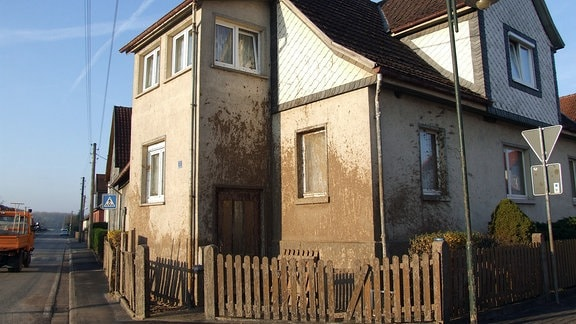 Blick auf ein Haus, dessen Häuserfassade mit braunen vergorenen Essensresten beschmutzt ist.