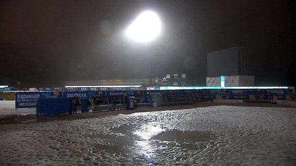 Die Ski-Arena in Oberhof wird von Fluchtlicht beleuchtet. Der Schnee ist von Regen aufgeweicht
