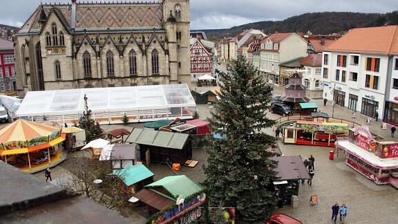 Blick von oben auf Marktplatz vor Kirche mit Weihnachtsmarktbuden und einem Karussell
