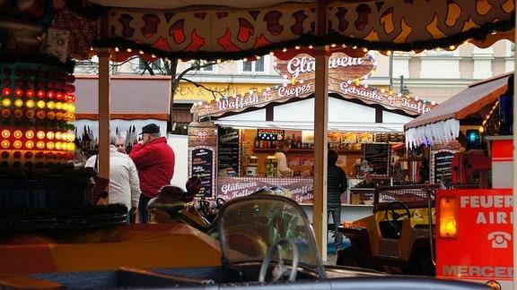 Weihnachtsmarktbuden, Karussell und einige dick angezogene Menschen davor