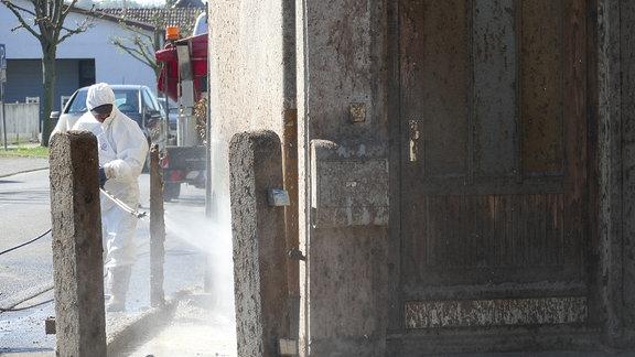 Ein Mitarbeiter eines Reiningungsunternehmens reinigt die Fassade eines Hauses in Schwallungen.