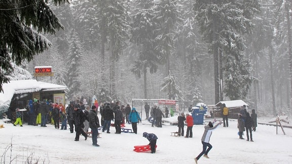 Kinder und Erwachsene stehen mit Schlitten im Schnee.