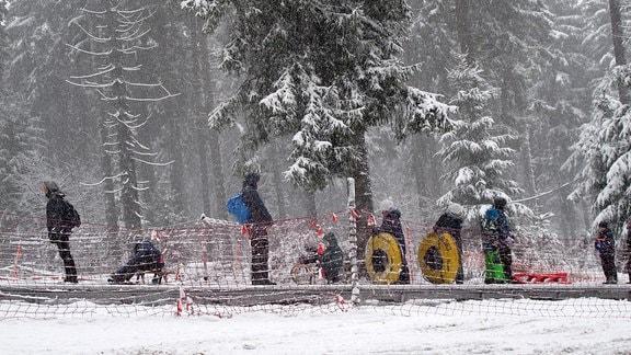 Kinder mit Schnee-Reifen stehen in einer Reihe.