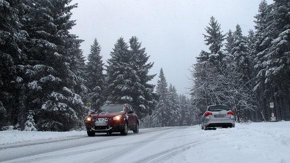 Zwei Autos auf einer schneebedeckten Straße.