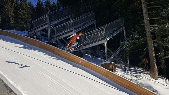 Ein Skispringer im Flug auf der Jugend-Skisprung-Schanze am Wadeberg bei Oberhof.