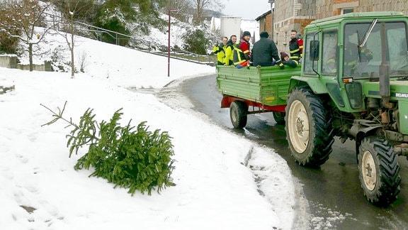 Ein Weihnachtsbaum im Schnee neben einer Traktor mit Anhänger