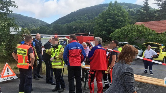 Mehrere Rettungskräfte stehen auf einem Platz.