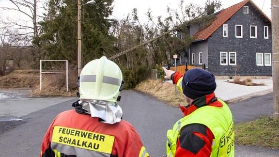 Zwei Einsatzkräfte beobachten eine Fichte, die auf einem Haus liegt