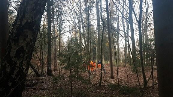 Menschen in orangenen Jacken durchstreifen das Gelände auf dem Friedhof in Zella-Mehlis