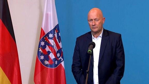 Thomas Kemmerich steht neben der Flagge von Thüringen.