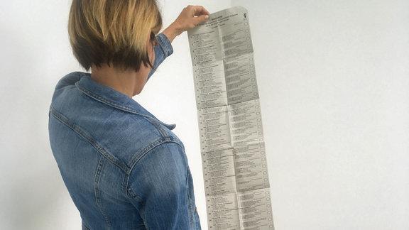 Ausgeklappter Stimmzettel einer Wahl in der Hand einer Person
