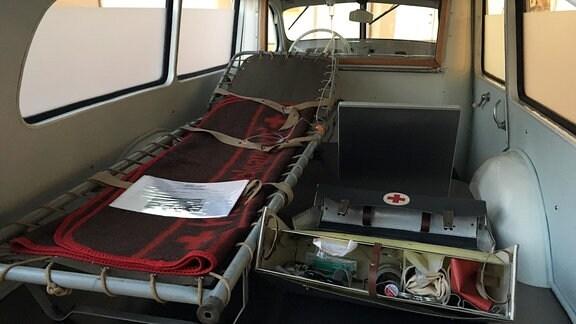Eine Pritsche im Inneren eines historischen Krankentransporters.