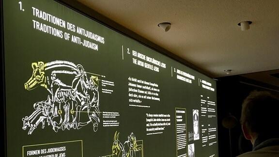 Eine schwarze Ausstellungswand, auf der in leuchtenden weißen und gelben Darstellungen die Judenfeindlichkeit zur NS-Zeit erklärt wird.