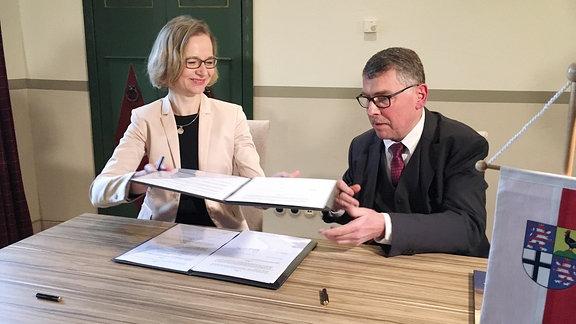 Katja Wolf, Oberbürgermeisterin von Eisenach, reicht ein Dokument an Reinhard Krebs, Landrat des Wartburgkreises, weiter.