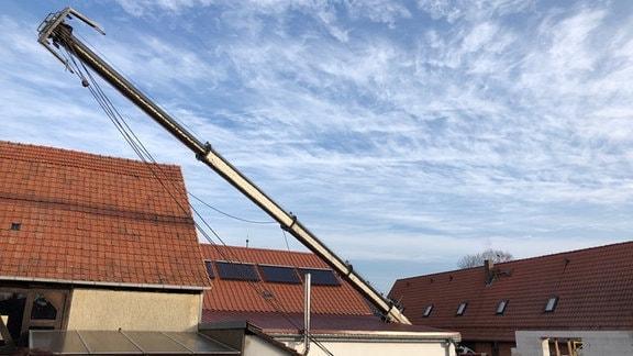 Ein Kran liegt quer auf dem Dach eines Hauses.