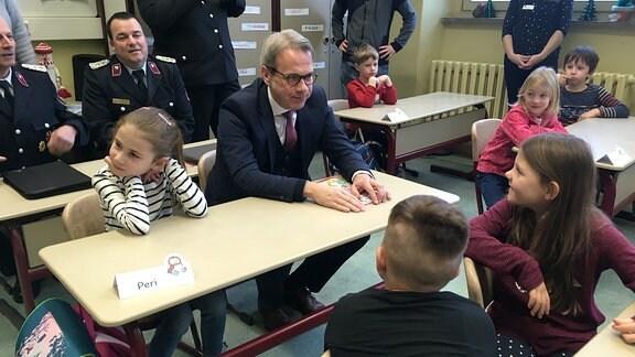 Mann in Anzug sitzt in Schulbank, umgeben von Kindern, dahinter Feuerwehrleute.
