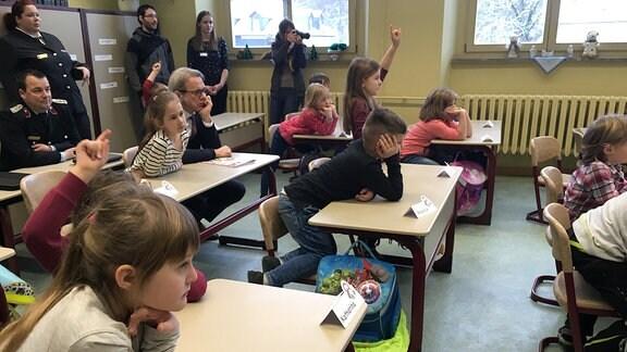 Kinder in Schulbänken gespannt nach vorn gebeugt.