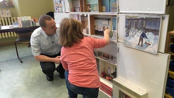 Mädchen und Feuerwehrmann vor Hausmodell.