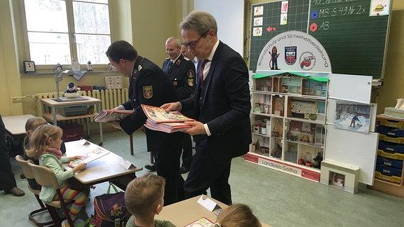 Feuerwehrleute und Mann in Anzug verteilen Hefte an Kinder.