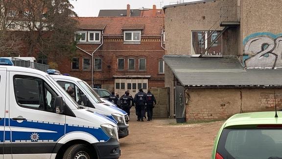Polizisten laufen über ein großes Fabrikgelände.