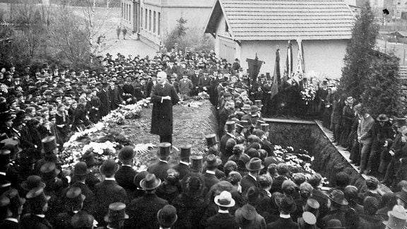 Auf einem historischen Foto sind viele Menschen bei einer Beerdigung zu sehen und ein Redner