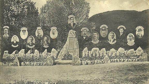 Auf einem historischen Foto ist ein Gedenkstein zu sehen und 15 Fotostafeln mit namentlich benannten Opfern