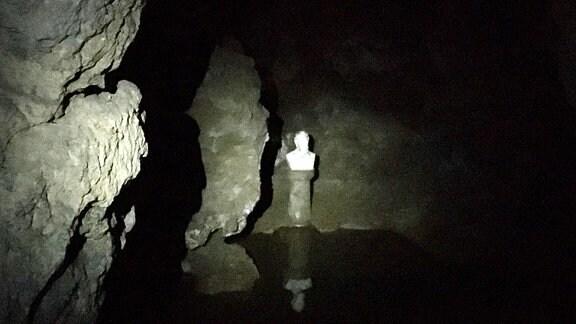 Ein dunkler Teich unter der Erde, an der Wand eine weiße Büste.