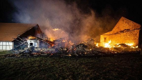 Flammen schlagen aus einem schon nahezu abgebrannte Wohnhaus. Die Feuerwehr versucht das Feuer zu löschen.
