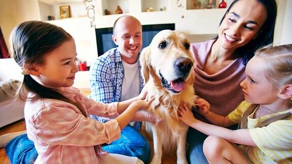 Familie streichelt einen Hund