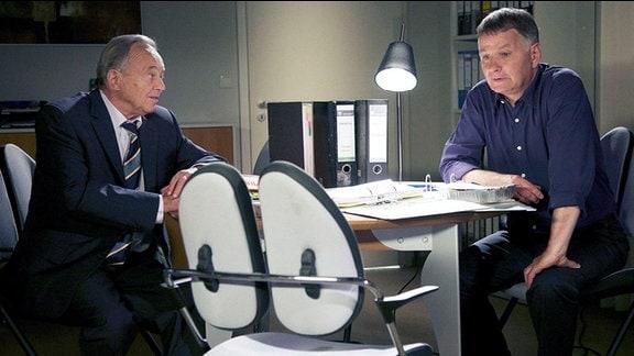 Zwei Männer beraten sich im schummrigen Büro