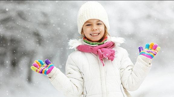 Ein Mädchen im Schnee mit Handschuhen.