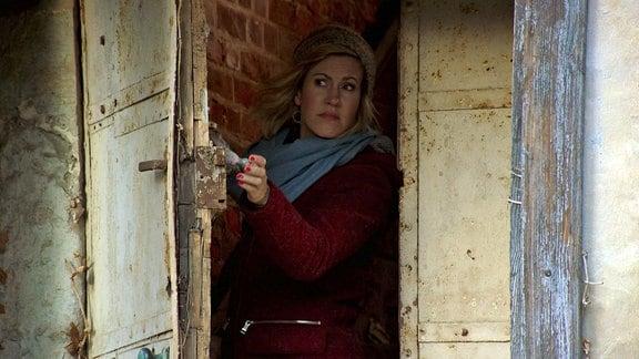 Eine Frau schaut durch eine alte Tür.
