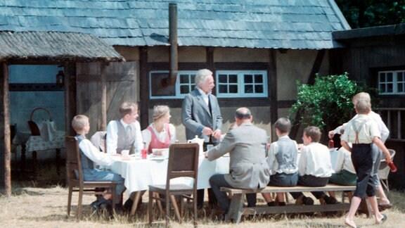 Gruppe junger Leute sitzt um einen deeckten Holztisch im Freien. Ein älterer Mann steht am Tisch und spricht.