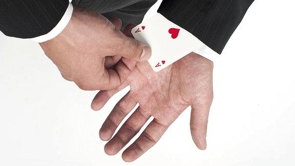 Mann im Anzug zieht sich ein Herz As aus dem Ärmel.