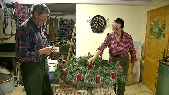 Ein Mann und eine Frau stehen an einem großen Adventskranz.