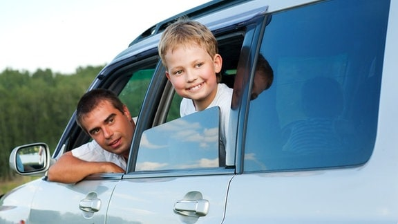 ein Vater und ein Junge schauen freudig aus ihrem Auto