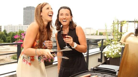 Zwei Frauen grillen auf einem Balkon.