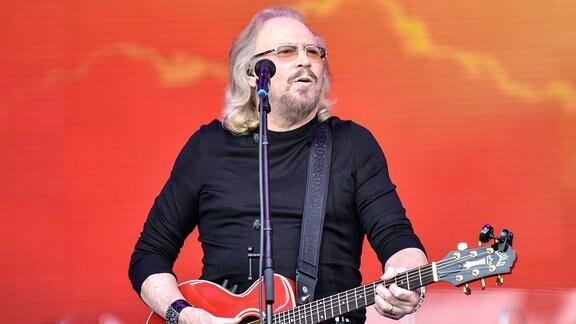 Ein Mann steht mit Gitarre auf einer Bühne und singt.